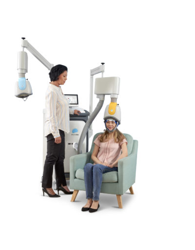 Shows a woman receiving TMS treatment with a Brainsway Deep TMS machine.